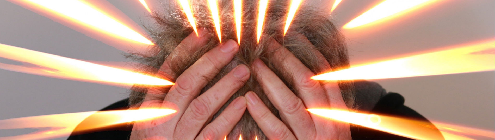 A person presses their hands to their head in frustration, outlined in streaks of orange light.