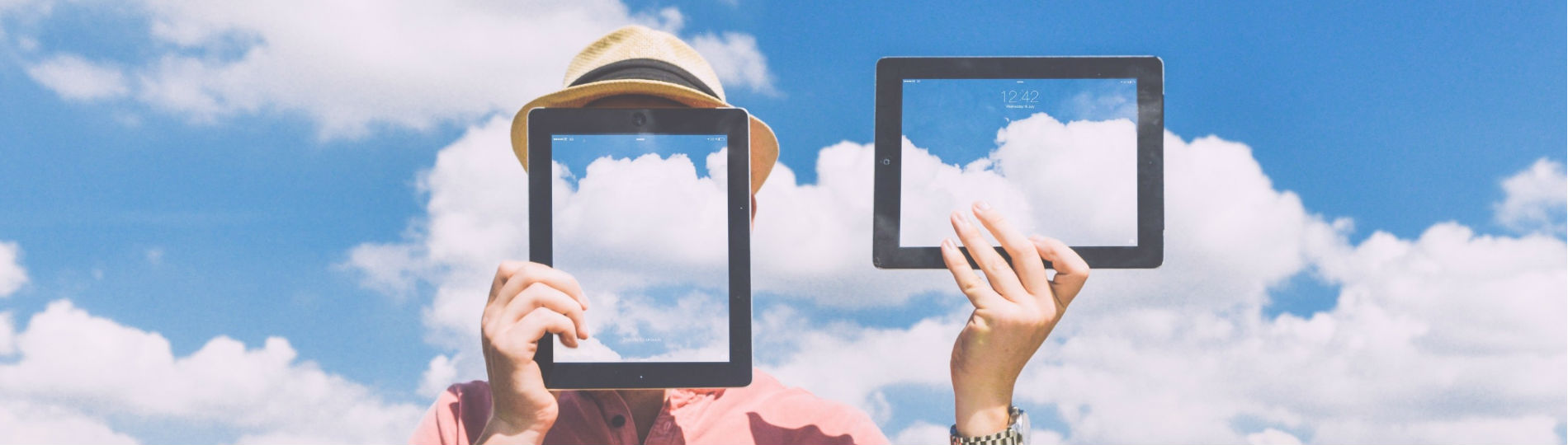 A man holds up two tablets reflecting the sky, one of which is blocking his face.