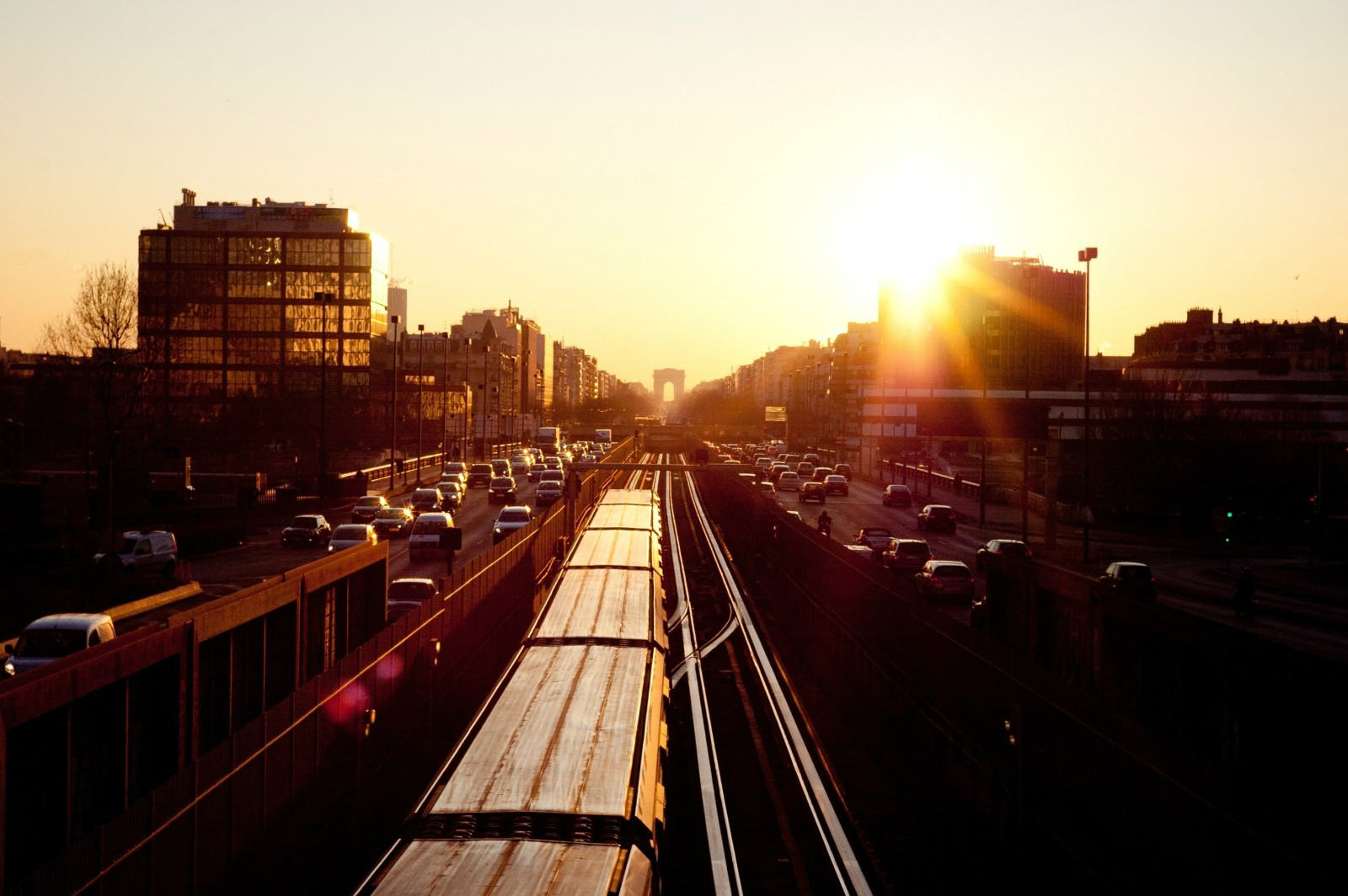 The sun sets over a train speeding through a busy city centre.