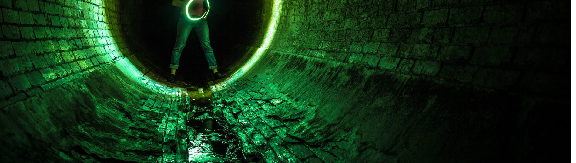A person holding a glowing green ring illuminates a stone tunnel.