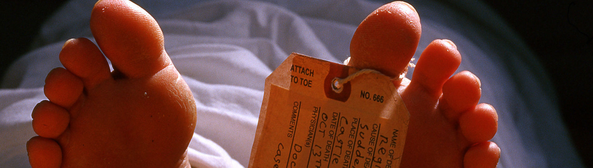A toe tag is attached to a deceased person's foot.