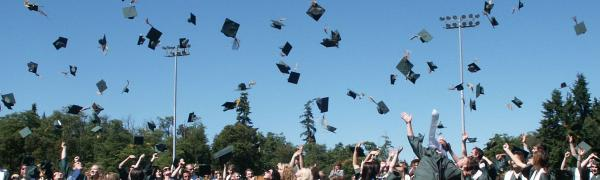 A crowd of people in graduation gowns throw their hats into the air.