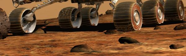 The wheels of the Mars Rover cross the planet's red soil.